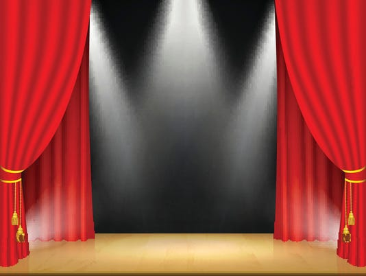 Theater stage with spotlights and red curtain.