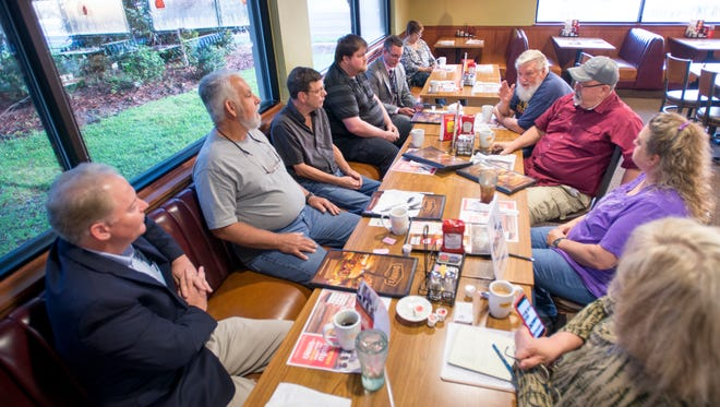 """District 1 Escambia County commissioner Jeff Bergosh, bottom left, listens as Rich Miller, top right, speaks during the monthly """"Coffee with the Commissioner"""" at Denny's in Pensacola on Tuesday, September 26, 2017."""