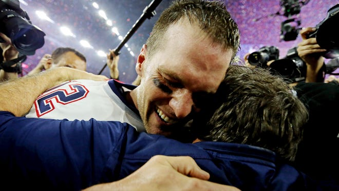New England Patriots head coach Bill Belichick and quarterback Tom Brady embrace after the game.