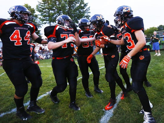 Marshfield Tigers' Braden Bohman(34), middle, celebrates a touchdown with his teammates during Friday opening game matchup between Wausau East and Marshfield at Beell Stadium in Marshfield.