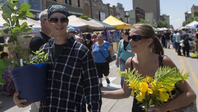 David Lautenschlager and Shelby Milock carry their purchases from the Oshkosh Saturday Farmer's Market on June 6.