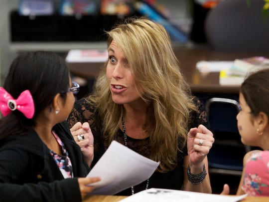 """Gateway Elementary School third grade teacher Kerri Toscano talks with students, Kylie Dutton and Deborah Melenez. Toscano uses a teaching method called """"whole brain learning,"""" which implements physical activity as a teaching tool. On the left is student Curtis Couillard."""