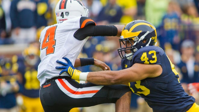Oregon State quarterback Seth Collins gets tackled after throwing a pass by Michigan defensive lineman Chris Wormley in the first quarter of the Wolverines' win on Sept. 12.
