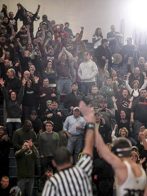 Eaton Rapids wrestling fans celebrate 135-pounder Hunter George's pin over Tyler Welch of St. Johns, sealing the Greyhounds' 34-27 Div. 2 Regional Championship February 18, 2015, at DeWitt.