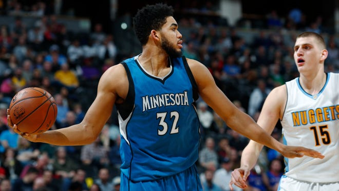 Minnesota Timberwolves center Karl-Anthony Towns, left, pulls in a rebound as Denver Nuggets forward Nikola Jokic defends during the second half of an NBA basketball game Wednesday, Feb. 15, 2017, in Denver. The Timberwolves won 112-99.