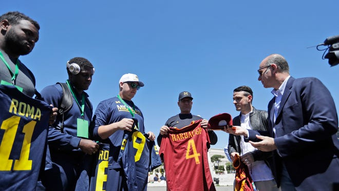 Michigan football team coach Jim Harbaugh is presented with a Roma jersey by Roma midfielder Alessandro Florenzi, second from right, prior to a training session at Rome's Stadio Dei Marmi.