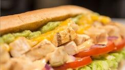 A Subway chicken sandwich with guacamole.