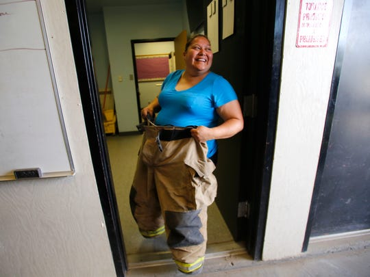 Volunteer firefighter Lisa Vecenti checks out her new gear at District 12, Shiprock Station 1.