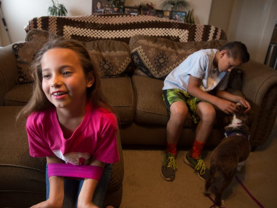 Kiera Schrock and her brother JJ Oliver play with Kiera's service dog Sugar at their home north of Farmington on Wednesday.
