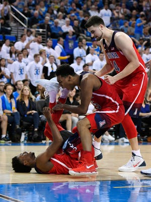 Arizona guard Kobi Simmons, left, celebrates with teammates guard Allonzo Trier, center, and center Dusan Ristic after forcing a turnover during the second half of an NCAA college basketball game against UCLA, Saturday, Jan. 21, 2017, in Los Angeles. Arizona won 96-85.