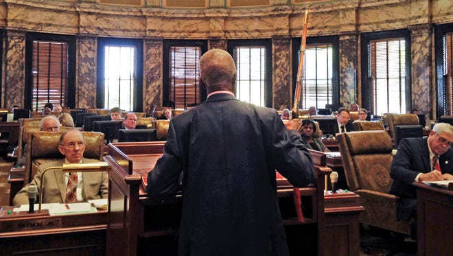 Sen. Hillman Frazier, D-Jackson, brandishes a sheathed sword Tuesday, March 29, 2016, during debate over House Bill 786, at the Capitol in Jackson, Miss. Frazier opposed the bill, which would grant immunity to trained church security teams that shoot people trying to commit violent crimes. Frazier said the bill went against Christian teaching, recounting the story of Jesus healing a servant of a high priest after a disciple cut off the servant's ear with a sword.