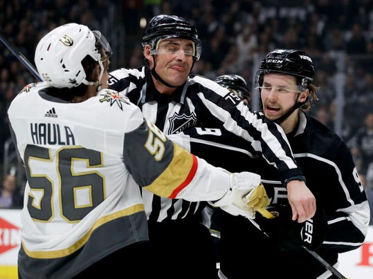 Linesman Derek Amell (75) separates Vegas Golden Knights left wing Erik Haula, left, and Los Angeles Kings left wing Adrian Kempe during the first period of Game 3 of an NHL hockey first-round playoff series in Los Angeles, Sunday, April 15, 2018. (AP Photo/Chris Carlson)
