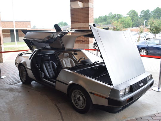 """A DeLorean, like that used as a time machine in the 1980s movie """"Back to the Future,"""" was on display for Pineville High School's parents' night that had a """"Back to the Future""""/1980s theme. Many stopped to take photos with the iconic car."""