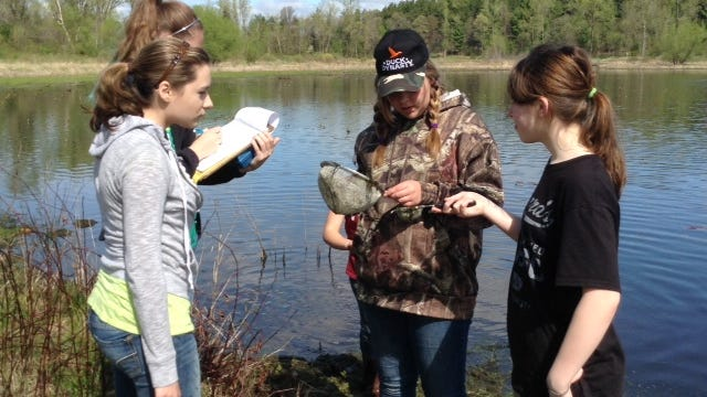 Students from Almond-Bancroft Middle School explore Bass Lake on May 22 during a field trip.