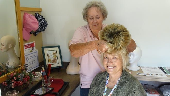 Frieda Barnhart (back) and Anne Campbell show the various colors and designs of wigs available for patients in the wig shop at the Adena Cancer Center.