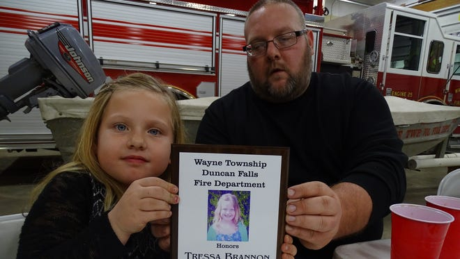 Tressa Brannon, left, and her father Brent Brannon showed off the award Tressa received for saving her brother from drowning last November. The seven-year-old said she was just happy to help out.