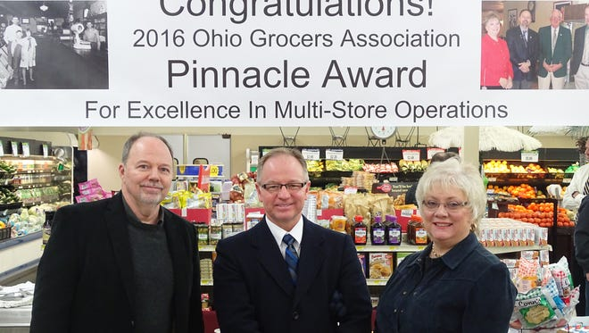Tuscarawas County Commissioner Chris Abbuhl, center, joins Gary Baker, left, and Terrie Baker, right, Tuesday during ceremonies honoring the Baker's five grocery stores as winners of the 2016 Ohio Grocers Association Pinnacle Award for excellence in multi-store operations.