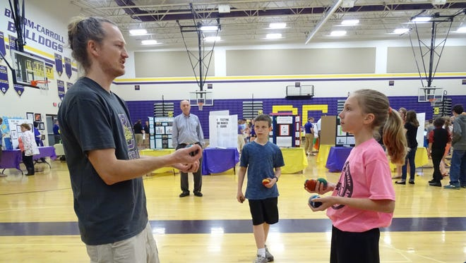 Bloom-Carroll high school teacher Keith Wentz teaches Emily Bratton, a fifth-grade student, to juggle at the district showcase Tuesday evening in the middle school gym.