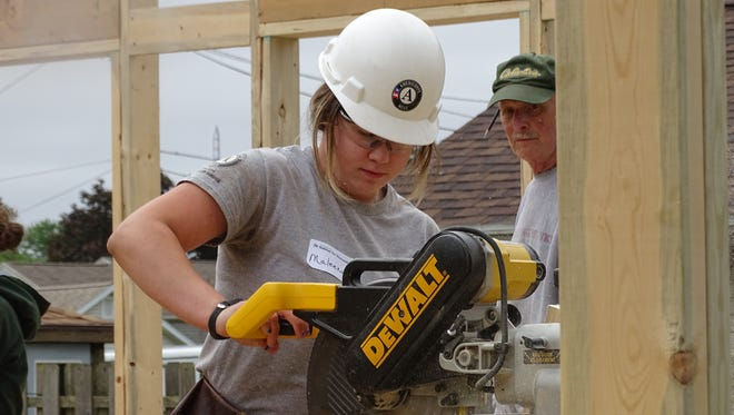 AmeriCorps volunteer, Maleena Aubut, 18, of Merrimack, New Hampshire, cuts a board for a Habitat for Humanity home in Fremont.