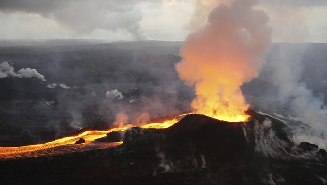 In this Saturday, July 14, 2018 photo provided by the U.S. Geological Survey, lava from Kilauea volcano erupts in the Leilani Estates neighborhood near Pahoa, Hawaii.