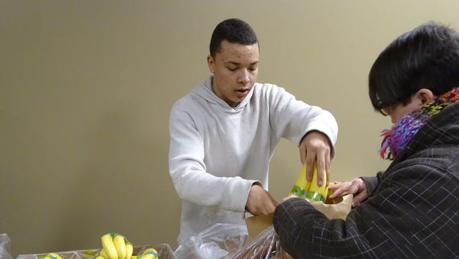 Draden Braxton, 17, hands out bananas during a food giveaway at Upper Assembly Room and Worship Center. The church, at 331 Main St., will give out items from the Mid-Ohio Foodbank at 5:30 p.m. every other Wednesday, with the next giveaway set for Jan. 21. Volunteers are needed to unload trucks and give out food.
