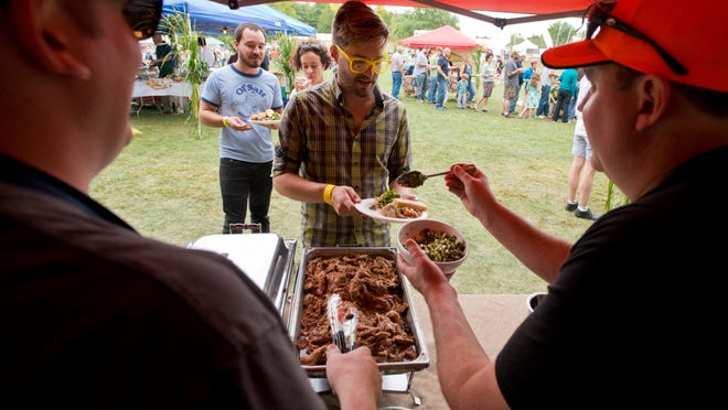 The Hen of the Wood's Will McNeil, left, and Eric Warnstedt serve up their slow-roasted calf at the EAT x NE food festival at Oakledge Park in Burlington on Sunday.