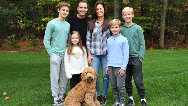 Chris Devin, second left, and his wife, Erica, center, are joined by their children from left, Declan, 15, Audrey, 7, Shane, 11, and Quinn, 13 and their dog, Murphy. The Norwell family raised over $60,000 for the Dana-Farber Cancer Institute, Wednesday, Oct. 28, 2020. Tom Gorman/For The Patriot Ledger