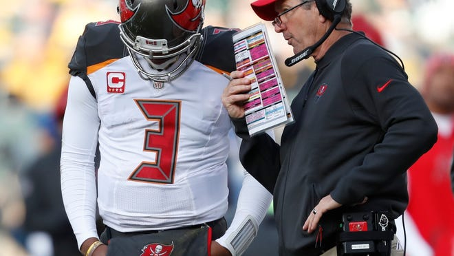 Tampa Bay Buccaneers head coach Dirk Koetter talks to quarterback Jameis Winston during the second half of an NFL football game against the Green Bay Packers Sunday, Dec. 3, 2017, in Green Bay, Wis. (AP Photo/Matt Ludtke)