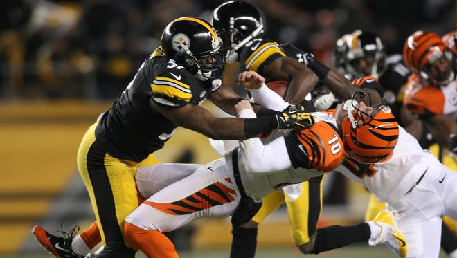 Pittsburgh Steelers linebacker Terence Garvin (57) tackles Cincinnati Bengals punter Kevin Huber (10) during the first quarter at Heinz Field.