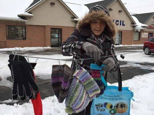 Laura Steele, associate director of Blue Water Center for Independent Living, hangs knitted winter items on a clothesline. The items are free to anyone who needs them.