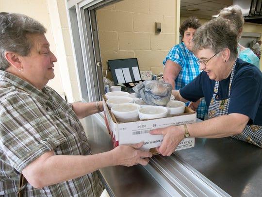 Dorothy Winter, left, buys 15 quarts of chicken corn