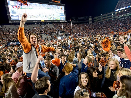 Auburn fans storm the field after Auburn defeated Alabama in the Iron Bowl in Auburn, Ala. on Saturday November 25, 2017. (Mickey Welsh / Montgomery Advertiser)