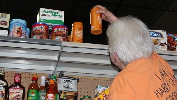 Linda Mitchell stocks the agency shopping area at the Harry Chapin Food Bank.
