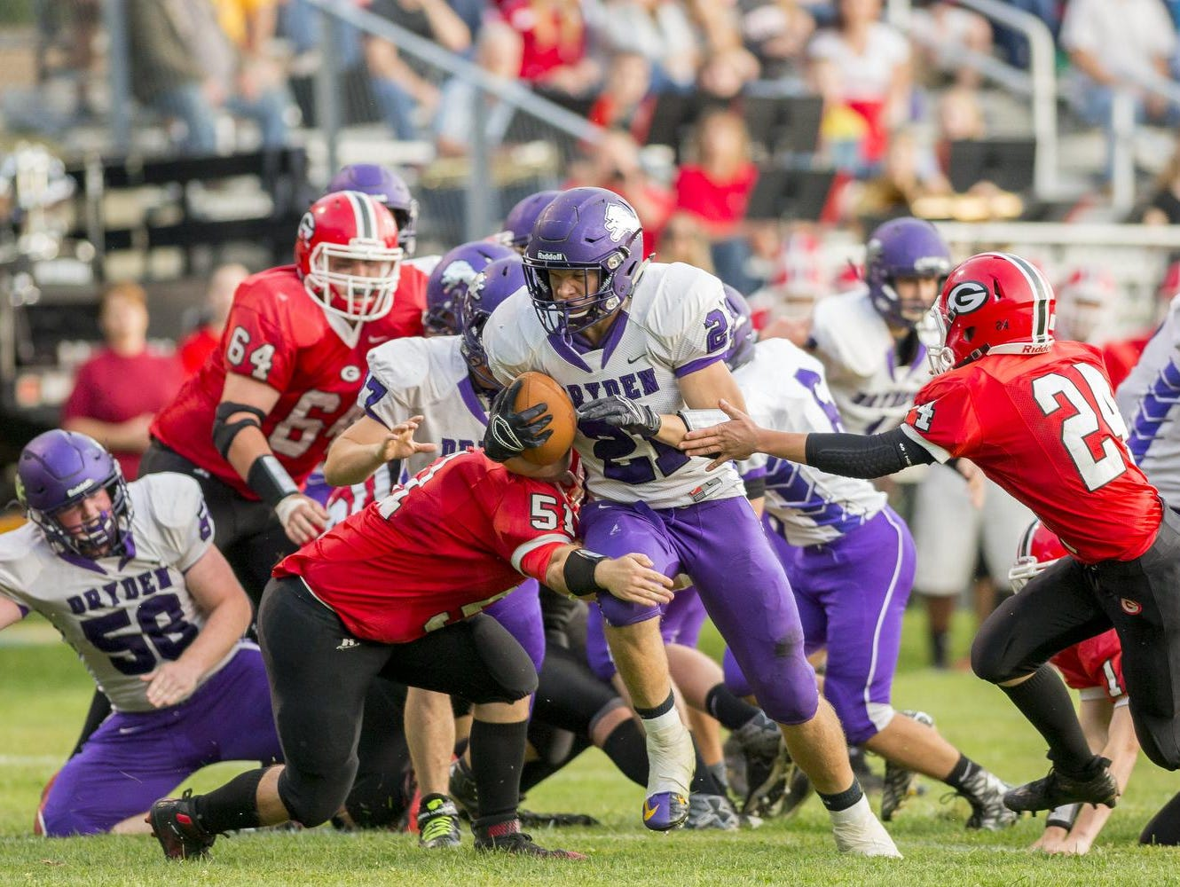 Dryden senior Stu Stahlman, center, breaks free from Groton's Keller Pai, left, and Adam Cronk on his way to scoring Dryden's first touchdown Friday evening at Ross Field in Groton. Stahlman had three touchdowns in the Purple Lions 39-34 defeat of the host Indians.