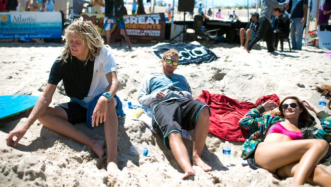 Jack Tenney, from left, Kyle Creager and Alex Tenney lounge in the sand and watch the competition.