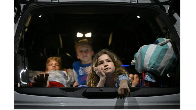"""Katinka Gerhardt, 8, of Watertown, front, and her brothers Joseph, 11, and Moritz, 12 watch Pixar's """"Onward"""" at the Mendon Twin Drive-In on May 28."""