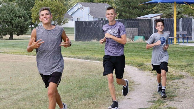 Collin Oswalt (left) runs with teammates during practice before the season. Oswalt finished second at state corss country in 2019.