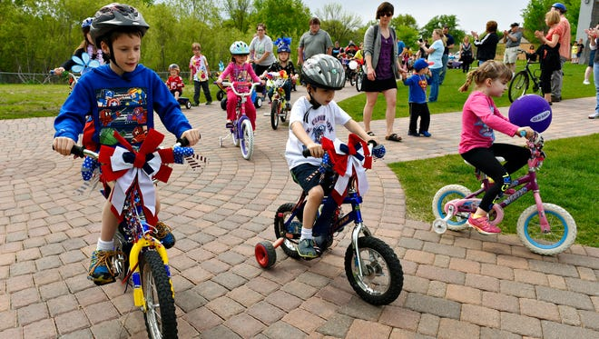 Children on decorated bicycles ride in a Memorial Day parade around Lake George in this 2015 photo.