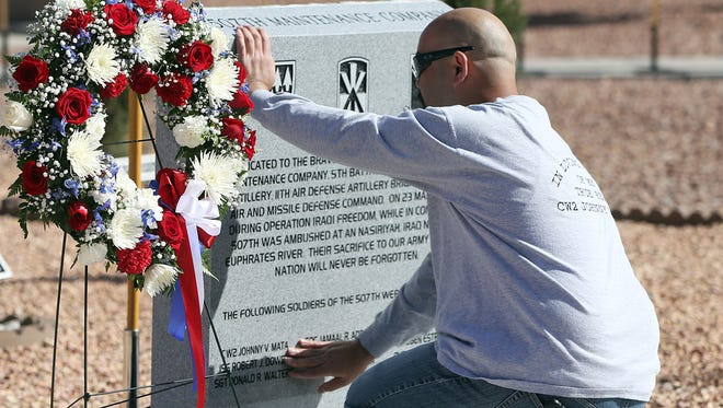 Joseph Hudson, a former member of the 507th Maintenance Company and a former prisoner of war, touches a new memorial dedicated Wednesday at headquarters of the 5th Battalion, 52nd Air Defense Artillery Regiment at Fort Bliss. The memorial honors nine of Hudson's fellow company members who died in a March 23, 2003, ambush during Operation Iraqi Freedom.