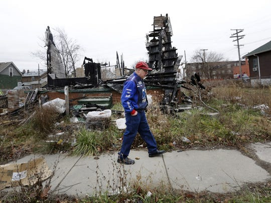 Richard Brown, 60, walks past a burned-out house next to his on Cabot Street in southwest Detroit. City officials said Brown should see neighborhood improvements soon.