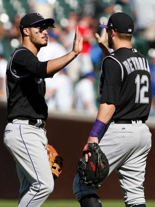 Colorado Rockies' Nolan Arenado, left, celebrates with Mark Reynolds after they defeated the Chicago Cubs in a baseball game Saturday, June 10, 2017, in Chicago. (AP Photo/Nam Y. Huh)
