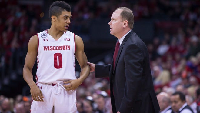 Wisconsin's D'Mitrik Trice talks with coach Greg Gard on the sidelines.
