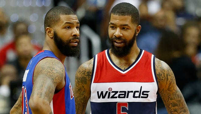 Marcus Morris (left), then of the Detroit Pistons, talks with his twin brother, Markieff Morris, of the Washington Wizards, during a game on Feb. 19, 2016, in Washington, D.C.