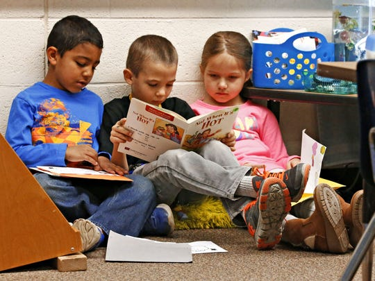 Three students practice reading at Apache Elementary