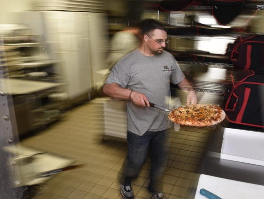Chris Raden boxes a pizza Friday at Flying Pig Pizza