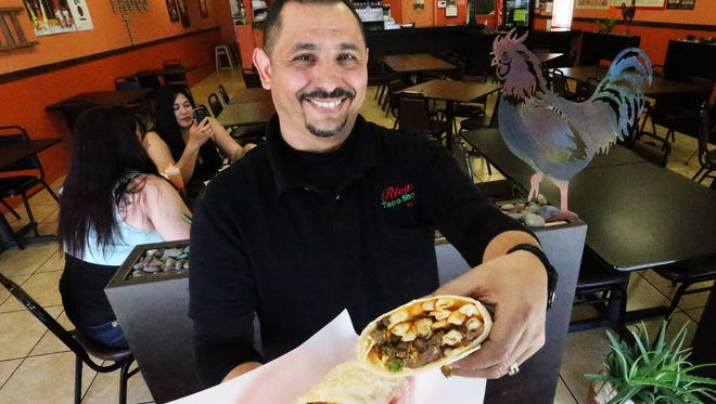 Robert Armendariz, co-owner with his wife, Judy, of Rivas Taco Shop, holds a California burrito in the restaurant at 1324 N. Zaragoza Road. Made with 8 ounces of carne asada, french fries, cheese and pico de gallo, the burrito is true to the Southern California-style staple his wife's family have made in San Diego and Phoenix.