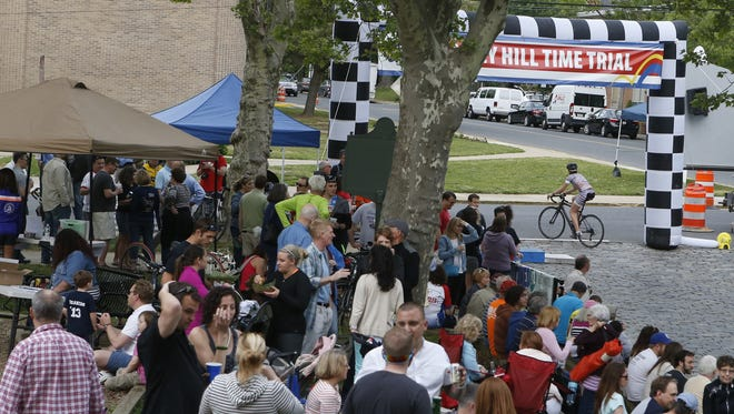 A competitor crosses the finish line of the Monkey Hill Time Trial as people gather in Brandywine Park in 2015.