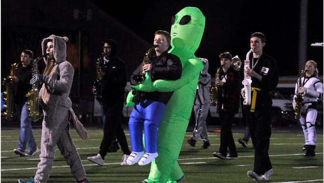 Wylie High School alto saxophone player Aaron Giles, dressed as person being carried by an alien, performs with the Pure Gold Band at halftime during the Oct. 27 game against Snyder High School. It being the final Friday before Halloween, both Snyder and Wylie perform their shows wearing individual costumes.