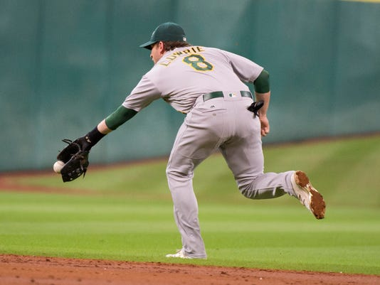 Oakland Athletics second baseman Jed Lowrie (8) stretches but can't field a ball hit by the Houston Astros Luis Valbuena in the second inning of a baseball game Thursday, July 7, 2016, in Houston. (AP Photo/George Bridges)