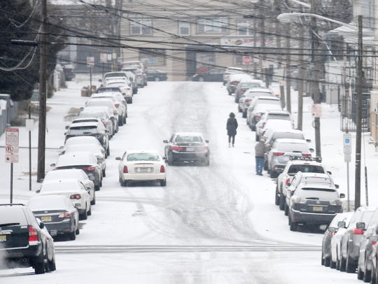 Cars and pedestrians navigate Sherman Ave. as snow